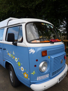 Blue vintage VW camper van with flower, butterfly and bird adornment